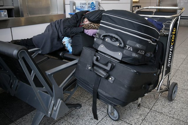 A woman sleeps next to baggage at LaGuardia Airport in New York January 26, 2015. (Photo by Shannon Stapleton/Reuters)