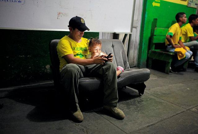 Rescue worker Josue Najarro and his niece look at a phone during the night shift at the Comandos de Salvamento base in San Salvador, El Salvador July 4, 2016. (Photo by Jose Cabezas/Reuters)