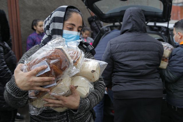 A woman carries traditional Christmas sweets in Bucharest, Romania, Thursday, December 24, 2020. Several poor families received food from donors on Christmas eve in one of the poorest areas of the Romanian capital. (Photo by Vadim Ghirda/AP Photo)