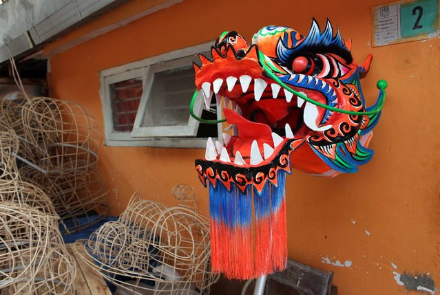 A dragon mask for the upcoming Lunar New Year hangs on the wall  at Lily Hambali's and lion masks and custome maker in Bogor, Indonesia, 02 February 2015. (Photo by Adi Weda/EPA)