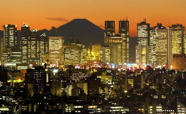 Skyscrapers in Tokyo's Shinjuku district frame Mt. Fuji at dusk in this December 11, 2002 file photo. (Photo by Kimimasa Mayama/Reuters)