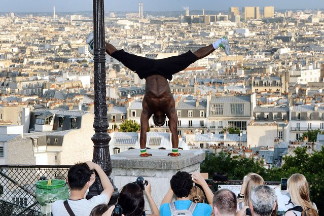 Guinea born Iya Traore, a former football player, juggler and acrobate performs in Paris, on August 6, 2013. (Photo by Pierre Andrieu/AFP Photo)