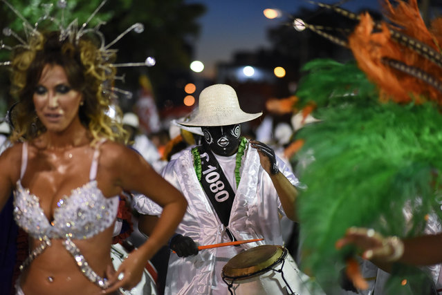 """A drummer and dancers perform at the """"Las Llamadas"""" parade for Carnival celebrations in Montevideo, Uruguay, Friday, February 6, 2015. (Photo by Matilde Campodonico/AP Photo)"""