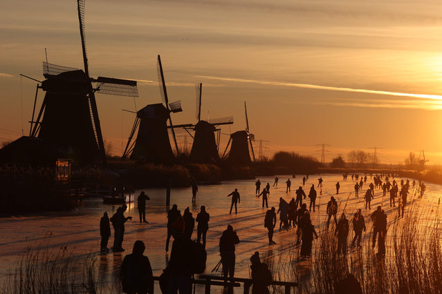 Skaters glide on the ice near windmills in the village of Kinderdijk on February 14, 2021. Skaters are called upon to skate as much as possible in their own neighborhood, to prevent crowds and thus the spread of Covid-19. (Photo by Kenzo Tribouillard/AFP Photo)