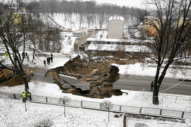 Onlookers examine the damage after a section of a road collapsed in Ostrowiec Swietokrzyski, southern Poland December 19, 2012. A hole, measuring 10 metres (33 ft) deep and at least 50 metres (164 ft) wide, appeared on a road in Ostrowiec Swietokrzyski over Tuesday night, reported by local media. (Photo by Pawel Malecki/Reuters/Agencja Gazeta)