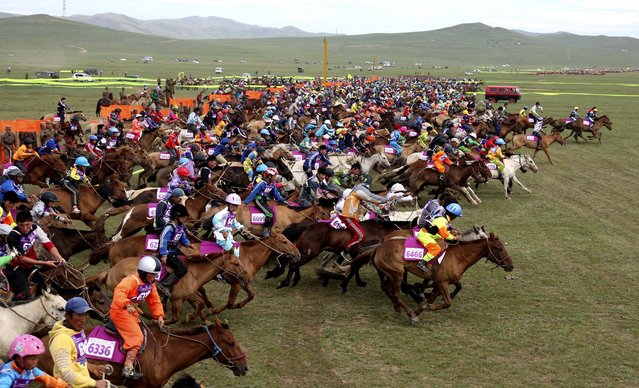 Participants compete in a horse race in Khui Doloon Khudag, Mongolia, on August 10, 2013. The race, which included 3000 horses, aimed to set a new Guinness World Record. (Photo by B. Rentsendorj/Reuters)