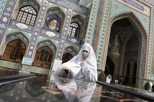A woman prays at the grave of an unknown soldier who was killed during 1980-88 Iran-Iraq war, at the shrine of Saint Saleh in northern Tehran, Iran, Tuesday, April 6, 2021. (Photo by Vahid Salemi/AP Photo)