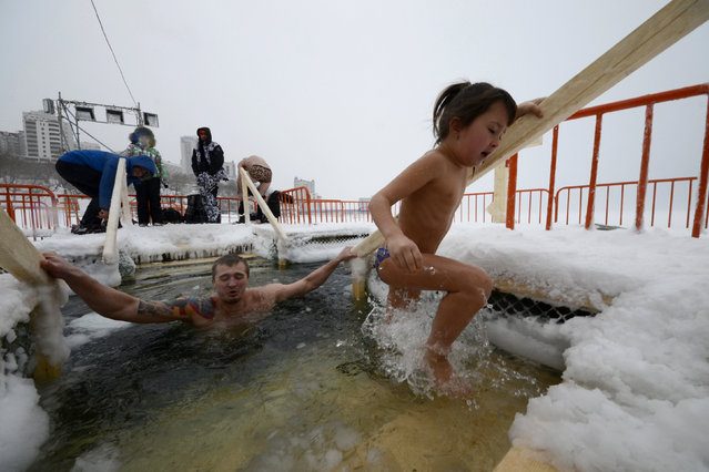 A man and a girl take a dip in icy waters during celebrations for the Orthodox Epiphany in the Sea of Japan in the far eastern city of Vladivostok, Russia, January 19, 2016. (Photo by Yuri Maltsev/Reuters)