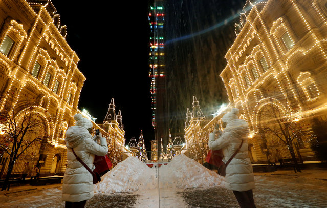 A woman takes photos next to the GUM department store decorated with lights for the upcoming Christmas and New Year holiday season at Red Square in Moscow, December 6, 2016. (Photo by Sergei Karpukhin/Reuters)