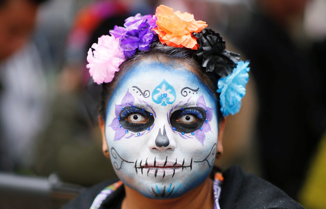 "A woman with her face painted as ""Catrina"", a Mexican character also known as ""The Elegant Death"", as he takes part in a Catrina parade ahead of the Day of the Dead in Mexico City, Mexico, October 21, 2018. (Photo by Andres Stapff/Reuters)"