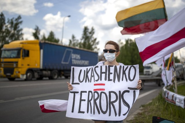 """A protester holds a banner reading """"Lukashenko – terrorist"""", old Belarusian and Lithuanian national flags during a protest demanding freedom for political prisoners in Belarus near Medininkai, Lithuanian-Belarusian border crossing east of Vilnius, Lithuania, Tuesday, June 8, 2021. Belarusian President Alexander Lukashenko has signed a law that threatens demonstrators with years in prison. It was the latest move in a relentless crackdown on protests against his rule. The law, which was signed Tuesday, envisages a prison sentence of up to three years for the participants in unsanctioned protests who had faced sanctions for joining them on at least two occasions over a year. (Photo by Mindaugas Kulbis/AP Photo)"""