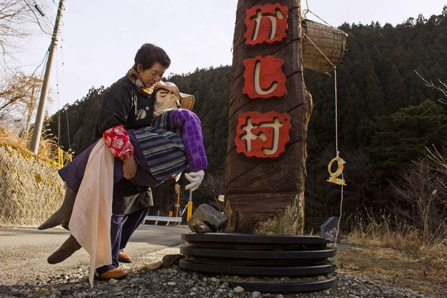 Tsukimi Ayano carries a scarecrow to place it on the road leading into the mountain village of Nagoro on Shikoku Island in southern Japan February 24, 2015. (Photo by Thomas Peter/Reuters)