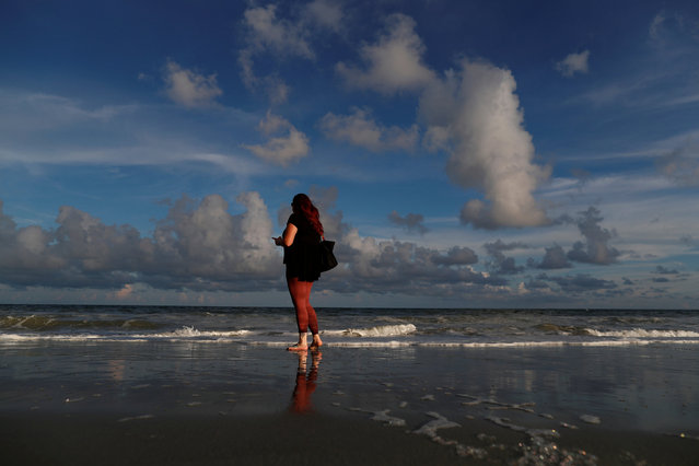 Caitie Sweeney of Myrtle Beach texts her family while visiting the beach ahead of the arrival of Hurricane Florence in Myrtle Beach, South Carolina, U.S. September 11, 2018. (Photo by Randall Hill/Reuters)