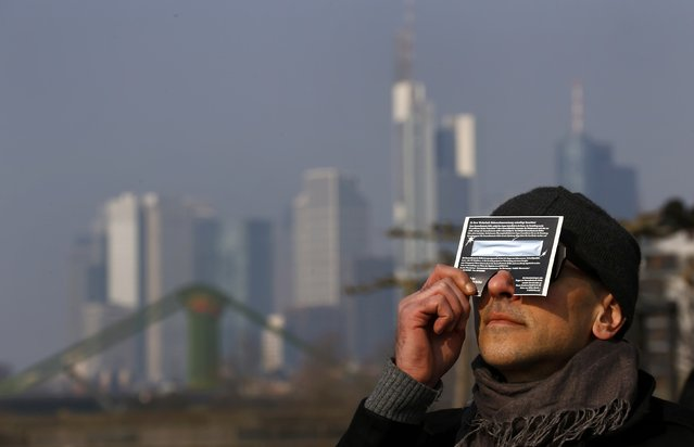 A man watches a partial solar eclipse looking through a protection foil shield as he sits on the terrace of a restaurant at the bank of river Main in front of the skyline of Frankfurt, March 20, 2015. (Photo by Kai Pfaffenbach/Reuters)