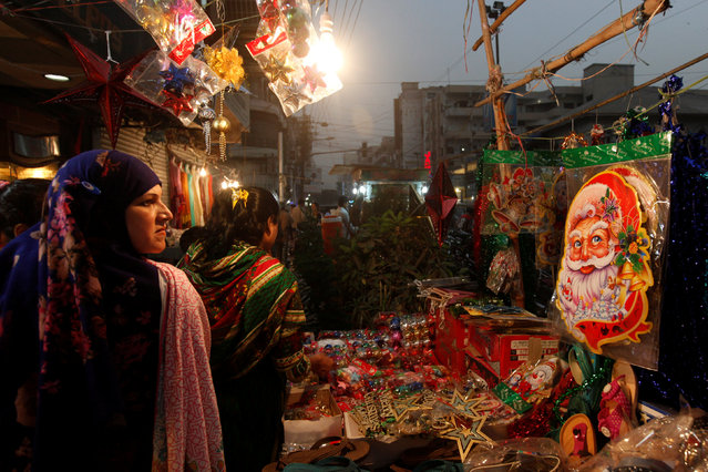 A Santa Claus decoration sticker hangs on a stall where women go through various items to buy for Christmas celebrations in Karachi, Pakistan, December 24, 2016. (Photo by Akhtar Soomro/Reuters)