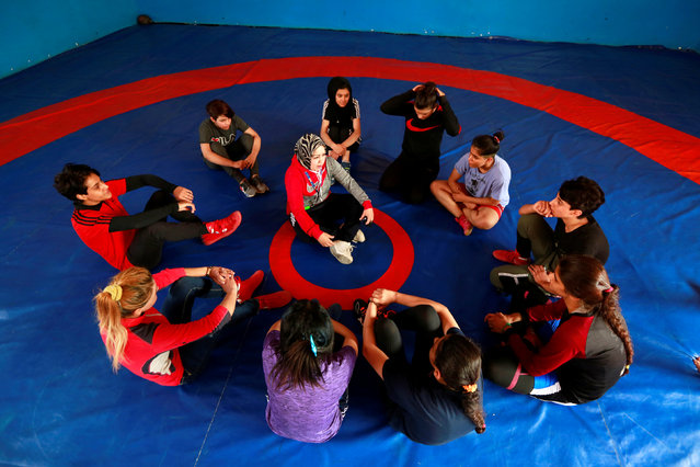 Coach Nihaya Dhaher Hussein sits surrounded by female wrestlers in Diwaniya, Iraq on November 10, 2018. The 50-year-old school teacher is the driving force behind the burgeoning team in Diwaniya which started in 2016. She drives the squad to practice, trains them and undertakes the dangerous task of convincing families to let their daughters, sisters or wives wrestle. (Photo by Alaa Al-Marjani/Reuters)
