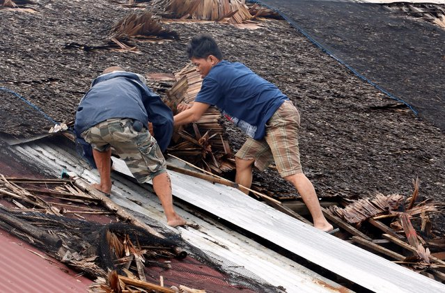 Residents fix their partially damaged roof after Typhoon Nock-Ten hit Mabini, Batangas in the Philippines December 26, 2016. (Photo by Erik De Castro/Reuters)
