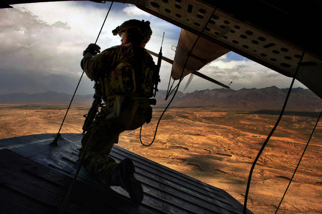 U.S. Air Force Tech. Sgt. Josh Martin, 438th Air Expeditionary Advisory Squadron, Mi-17 aerial gunner, provides rear security on a Mi-17 helicopter, Kabul, Afghanistan, May 31, 2014. Martin, a Rapid City, S.D. native, is deployed from the 55th Rescue Squadron, Davis Monthan Air Force Base, Ariz. The 438th AEAS and Afghan Air Force have combined efforts to train with about 300 Afghan commandos with the 8th Commandos Kandak. (Photo by Staff Sgt. Vernon Young/U.S. Air Force)