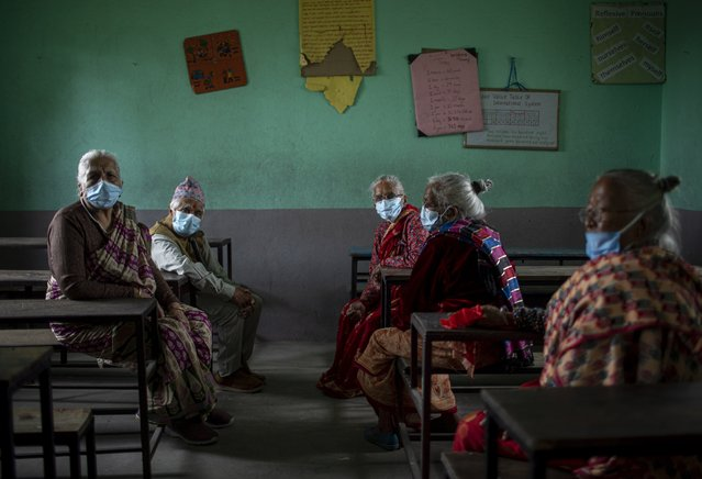 Elderly women sit inside a classroom as they wait to receive a second dose of Covishield COVID-19 vaccine at Karyabinayak School in Lalitpur, Nepal, 23 June 2021. The Lalitpur Metropolitan City started inoculating a second dose of Covishield vaccine for people over 77 years of age. (Photo by Narendra Shrestha/EPA/EFE)