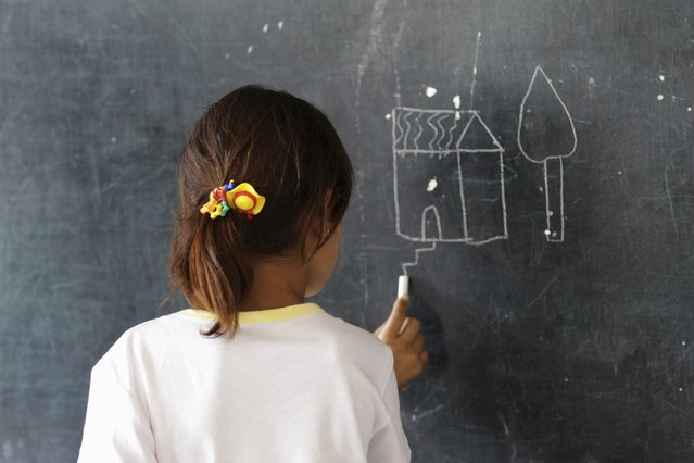 A girl draws on a blackboard inside a school in the southern countryside of Idlib, Syria September 20, 2015. (Photo by Khalil Ashawi/Reuters)