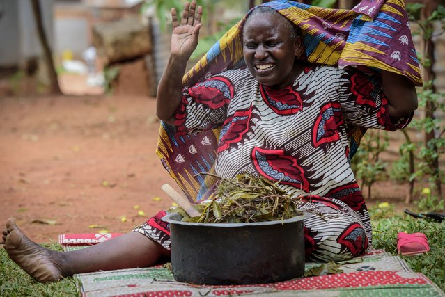 A woman reacts after covering herself to inhale steam from an infusion made from local herbs believed by her to prevent and treat the symptoms of COVID-19, in Kampala, Uganda on Tuesday, July 6, 2021. Some hospitals with COVID-19 wards are charging prohibitive sums for most Ugandans and many are now self-medicating within their homes, experimenting with everything from traditional medicine to a newly approved herbal remedy selling briskly as COVIDEX. (Photo by Nicholas Bamulanzeki/AP Photo)