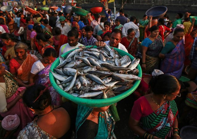 A woman carries fish for sale at a wholesale market at a harbour in Mumbai, March 16, 2015. India's wholesale prices declined at a much faster-than-expected pace of 2.06 percent on year in February, their fourth straight monthly fall, on the back of plunging global oil prices, government data showed on Monday. (Photo by Danish Siddiqui/Reuters)