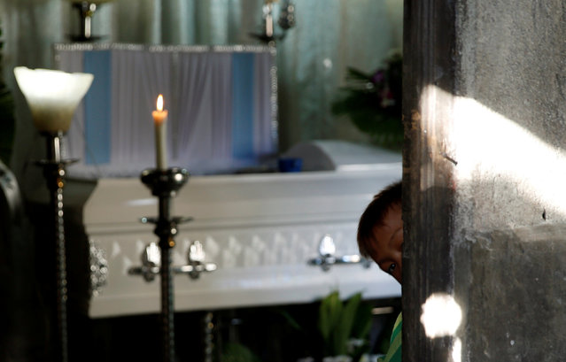 Jay looks outside as he stands near the coffin of his elder brother Jonel Segovia, who was shot dead by suspected vigilantes at a house storing illegal narcotics, police said on Thursday, in Caloocan city, Metro Manila, in the Philippines December 29, 2016. (Photo by Erik De Castro/Reuters)