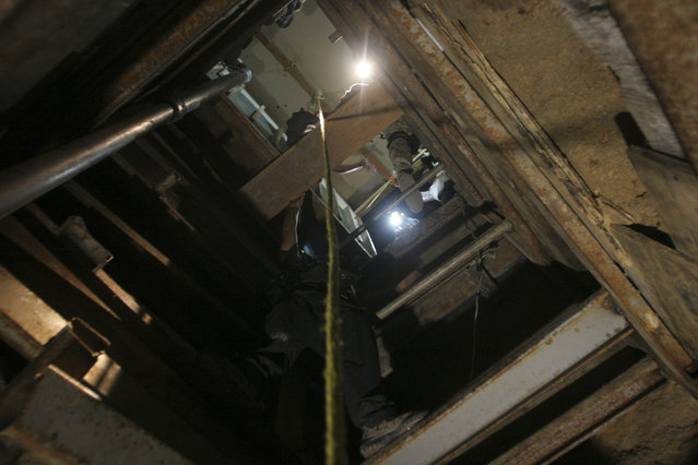A journalist climbs the shaft of a cross border tunnel located by the Mexican army at a warehouse in Tijuana July 12, 2012. (Photo by Jorge Duenes/Reuters)