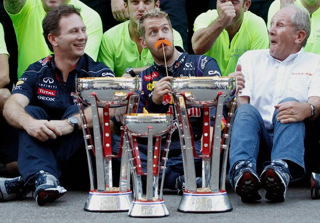 Red Bull Formula One driver Sebastian Vettel of Germany (C) jokes as he celebrates his win with the Red Bull team after the Austin F1 Grand Prix at the Circuit of the Americas in Austin November 17, 2013. (Photo by Mike Stone/Reuters)