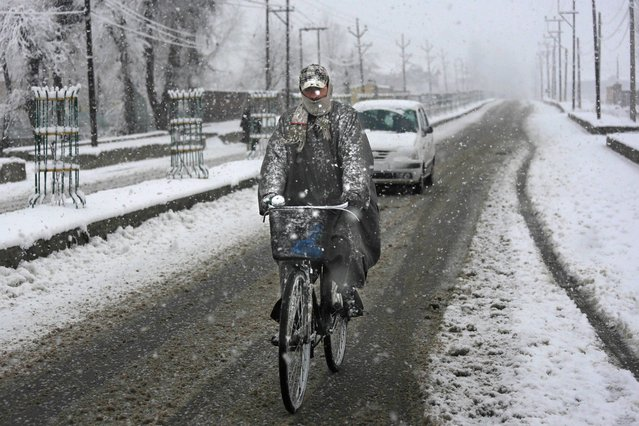 A cyclists rides through snowfall on the outskirts of Srinagar, India, Tuesday, December 31, 2013. Snowfall in the Indian portion of Kashmir has disrupted power supply, air traffic and road traffic between Srinagar and Jammu, the summer and winter capitals of India's Jammu-Kashmir state, according to news reports. (Photo by Dar Yasin/AP Photo)