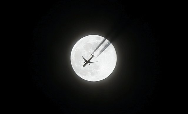 A plane flies as the Supermoon is seen in Brussels, Belgium on February 20, 2019. The Supermoon is a full moon that almost coincides with the closest distance that the Moon reaches to Earth in its elliptic orbit, resulting in a larger-than-usual visible size of the lunar disk as seen from Earth. (Photo by Dursun Aydemir/Anadolu Agency/Getty Images)