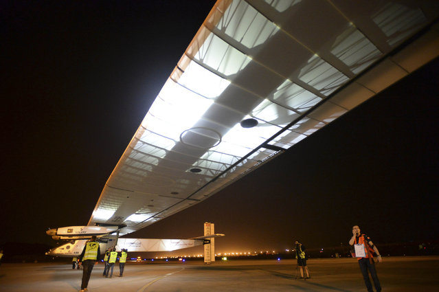 Workers guide a solar-powered plane out of a hangar at Jiangbei International Airport in southwest China's Chongqing Municipality, Tuesday, April 21, 2015. (Photo by Chinatopix via AP Photo)