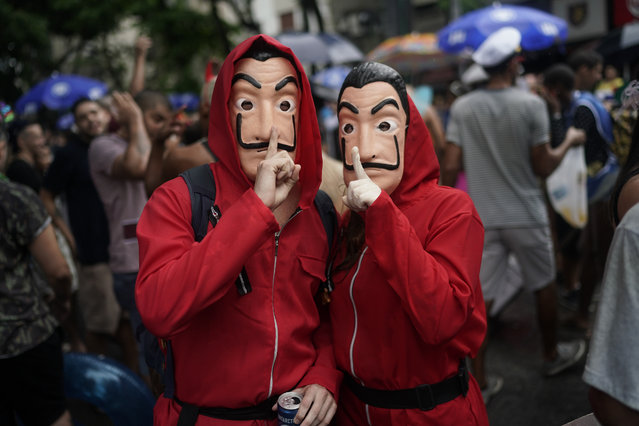 "In this Saturday, February 16, 2019 photo, carnival revelers dressed as characters from the movie ""La Casa de Papel"" pose for a picture during the ""Desliga da Justica"" block party in Rio de Janeiro, Brazil. ""Desliga"" means in Portuguese to turn something off, and this street party is a parody of the Justice League. (Photo by Leo Correa/AP Photo)"