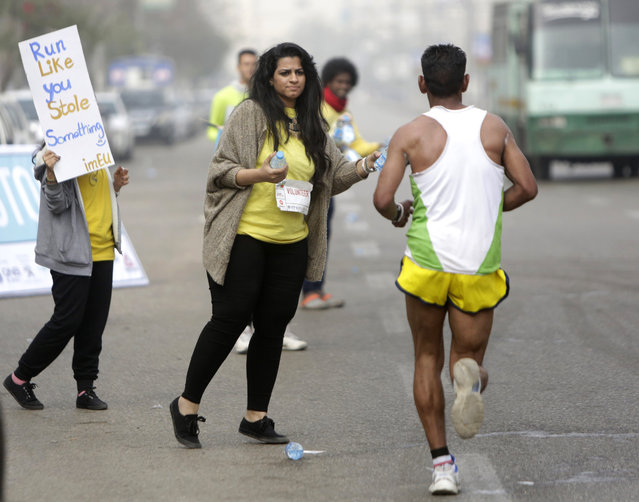 In this Friday, April 17, 2015 photo, Egyptian volunteers at a water stop offer water to runners participating in Cairo's annual Half Marathon in the Heliopolis district in Cairo, Egypt. Young Egyptians are once again organizing on social media and taking to the streets of Cairo by the hundreds every Friday, not to protest injustice or clash with police, but to enjoy long runs through one of the world's most crowded and chaotic cities. (Photo by Amr Nabil/AP Photo)