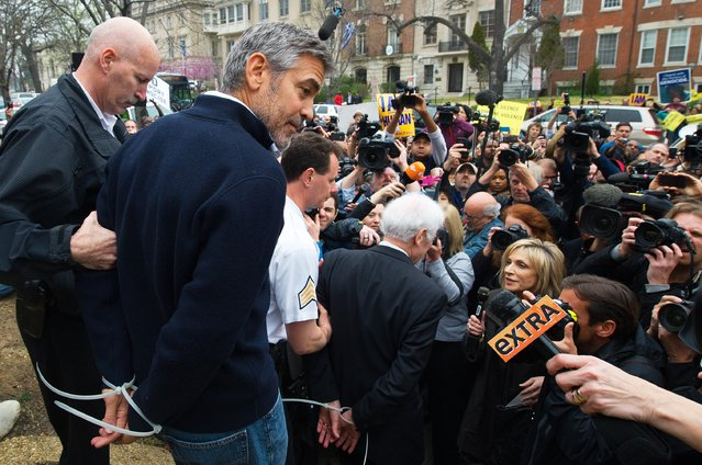 Actor and activist George Clooney (2nd L) and his father journalist Nick Clooney (C) are arrested for trespassing upon the Sudanese Embassy in Washington, DC, on March 16, 2012. Clooney and his father were protesting against human rights abuses by the Sudanese government. (Photo by Paul J. Richards/AFP Photo)