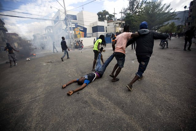 Demonstrators drag the body of a fellow protester toward police, as a form of protest after police shot into the crowd in which he died, during a demonstration demanding the resignation of Haitian President Jovenel Moise near the presidential palace in Port-au-Prince, Haiti, Tuesday, February 12, 2019. Protesters are angry about skyrocketing inflation and the government's failure to prosecute embezzlement from a multi-billion Venezuelan program that sent discounted oil to Haiti. (Photo by Dieu Nalio Chery/AP Photo)