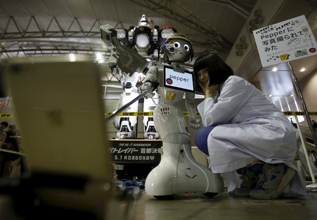 "SoftBank Corp's humanoid robot named ""Pepper"" takes a ""selfie"" photo with a large robot (L in background) from the Japanese live action film series ""The Next Generation – PatLabor"" and its application designer (R) at a booth during Niconico Chokaigi 2015 in Makuhari, east of Tokyo, Japan April 26, 2015. (Photo by Yuya Shino/Reuters)"