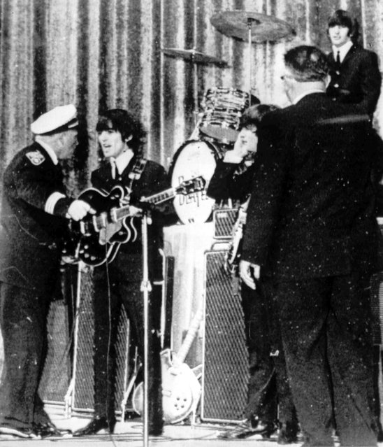 Police Inspector Carl Bear of Cleveland's Juvenile Bureau, left, orders George Harrison and the other members of the British pop group The Beatles, off the stage of the Public hall, Cleveland, Ohio, September 16, 1964 as teenagers rushed the stage. Bear let the group back on ater wailing youngsters were given 15 minutes to cool down. From left to right, Bear, Harrison, John Lennon, unknown, and Ringo Starr, top right. (Photo by AP Photo)