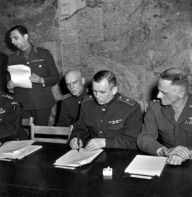 In this May 7, 1945 file photo, Gen. Ivan Susloparoff, Russian chief of staff, signs the unconditional surrender terms to Germany, negotiated at Reims, France. At left is his aide, Lt. Gen. Ivan Chermieff, and at right, Lt. Gen. C.A. Spaatz, USAAF. (Photo by Ralph Morse/Pool Photo via AP Photo)