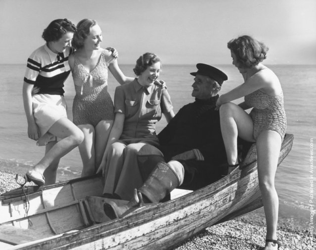 Bathing beauties cluster round a fisherman as he regales them with his fishy tales, 1939