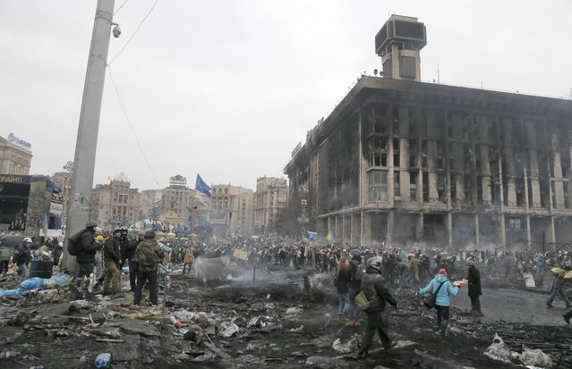 People pass through Independence Square, the epicenter of the country's current unrest, Kiev, Ukraine, Thursday, February 20, 2014. (Photo by Efrem Lukatsky/AP Photo)