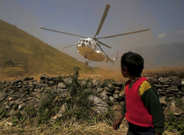 A child looks on as a helicopter lands to drop food supplies after the April 25 earthquake in Kerauja, Nepal, May 8, 2015. (Photo by Olivia Harris/Reuters)