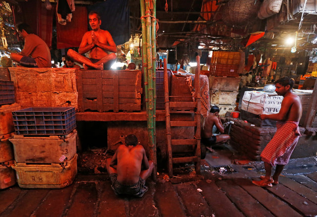 A worker prays as others prepare to take a bath at a wholesale fish market in Kolkata, India February 9, 2017. (Photo by Rupak De Chowdhuri/Reuters)