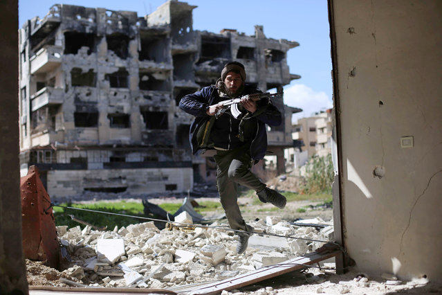 A fighter belonging to Jaish al-Islam (Islam Army) runs to take cover near the frontline on March 14, 2016 in the neighbourhood of Jobar, on the eastern outskirts of the capital Damascus. (Photo by Amer Almohibany/AFP Photo)