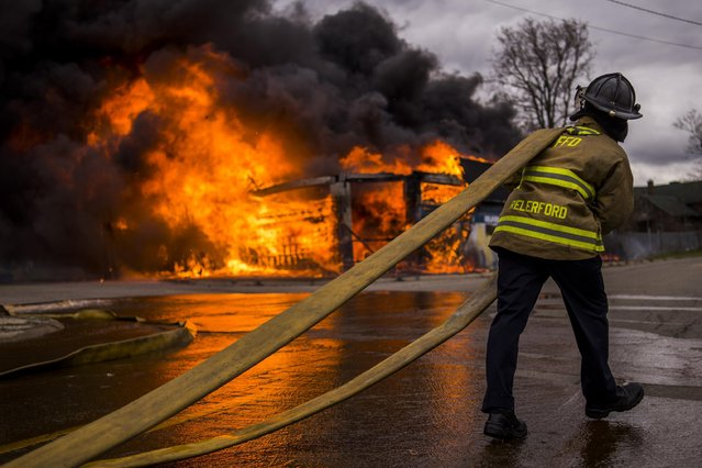 Flint firefighters work to contain a large fire that engulfs a former strip club, once called The Body Shop, Wednesday, April 22, 2015 at the intersection of Glenwood Avenue and Asylum Street, sending a large plume of black smoke over the city of Flint. (Photo by Jake May/The Flint Journal-MLive.com via AP Photo)