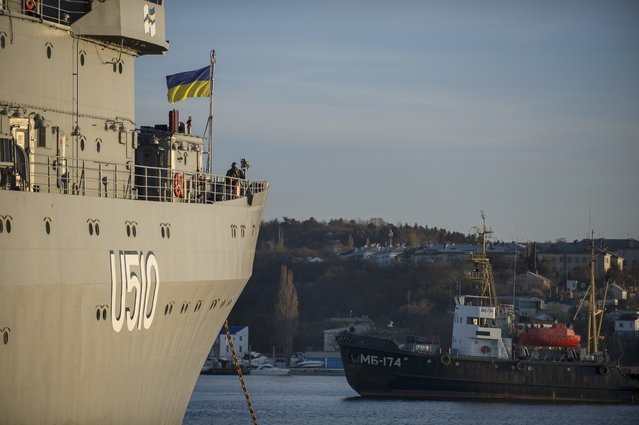 A Ukrainian national flag flies on the board of  Ukrainian navy ship Slavutich at harbor of  Sevastopol, Ukraine, Monday, March 3, 2014. The Ukrainian Defense Ministry said that Russian forces that have overtaken Ukraine's strategic region of Crimea are demanding that the ship's crew surrender. (Photo by Andrew Lubimov/AP Photo)