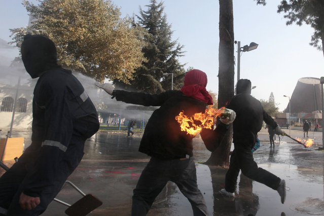 A masked demonstrator readies to throw a petrol bomb towards the police during a protest at the University of Santiago, in Santiago, Chile, Thursday, May 14, 2015. In the capital and other cities across the country, high school and university students marched, for the second time this year, to demand education reform. (Photo by Luis Hidalgo/AP Photo)