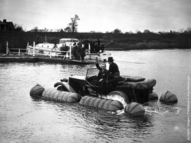 1931:  Captain Malin with an amphibian Riley car going down the Severn