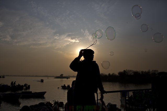 A Pakistani vendor releases bubbles to attract customers visiting Lake View park in Islamabad, Pakistan, Saturday, January 24, 2015. (Photo by Muhammed Muheisen/AP Photo)