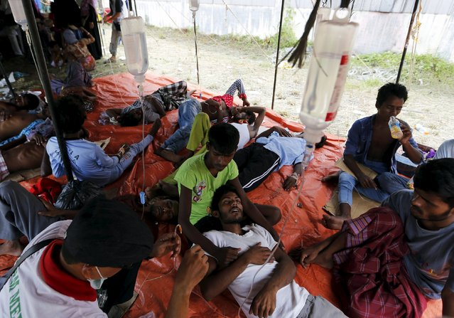 An Indonesian paramedic (L) gives medical treatment to a Rohingya migrant who arrived in Indonesia by boat inside a temporary shelter in Kuala Langsa in Indonesia's Aceh Province May 16, 2015. (Photo by Reuters/Beawiharta)